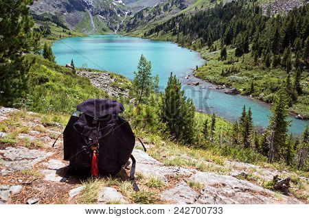 Black Backpack Lying On The Stone Against A Mountain Landscape With Turquoise Lake. Backpacking In T
