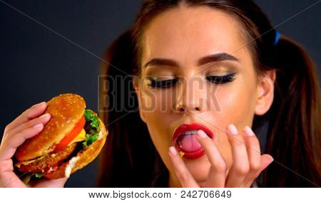 Woman eating hamburger. Girl loves fast food. Student consume fast food. Portrait of person with good appetite have greedily dinner delicious sandwich. She can not refuse harmful products.