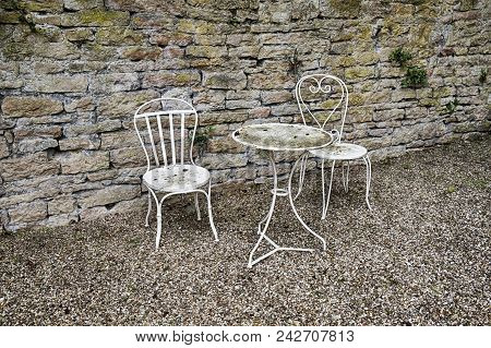 A White Table And Two Chairs Form A Nice Quiet Area In A Small Garden Court In The Town Of Beaune In