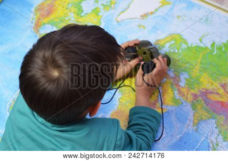 Kid Is Looking Through Binoculars Around. Adventure And Travel Concept. Joyful Background. Child Is