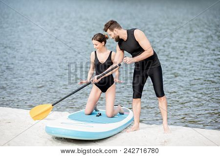Male Coach Teaching Young Woman To Surf On The Standup Paddleboard With Oar Standing On The Beach