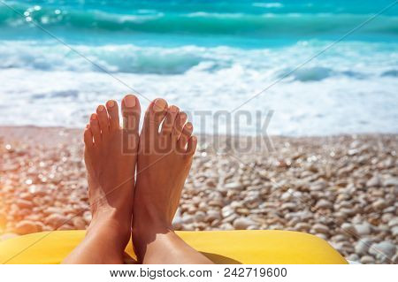 Closeup photo of a women's feet with nice pedicure lying down on stony seashore, conceptual photo of summer vacation on the beach