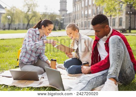 Busy undergraduates. Three busy undergraduates feeling overloaded while preparing their home assignment sitting on the grass together poster
