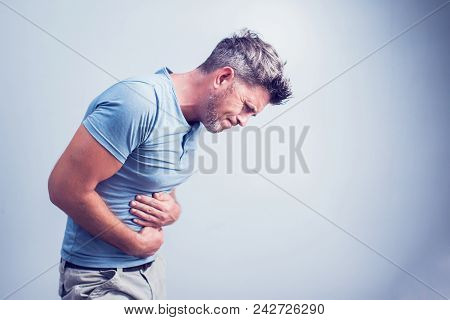 People, Healthcare And Health Problem Concept - Unhappy Man Suffering From Stomach Ache Over Gray Ba