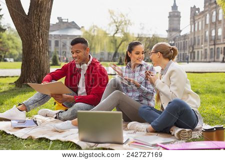 Busy Student. Smiling Pretty Girls Sitting Near Their Busy Fellow Student Preparing For Important Te