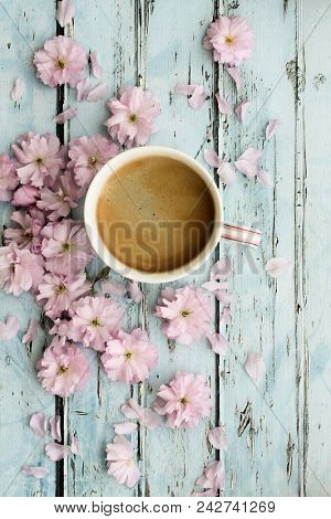 Coffee and pink cherry blossoms on a rustic wooden background