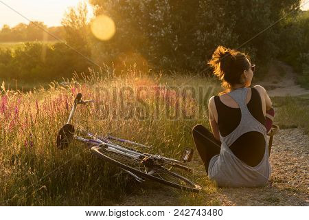 Summer Sunset In Countryside. Sunset Light In Countryside. Girl Sitting In Field In Sunset. Girl Rel