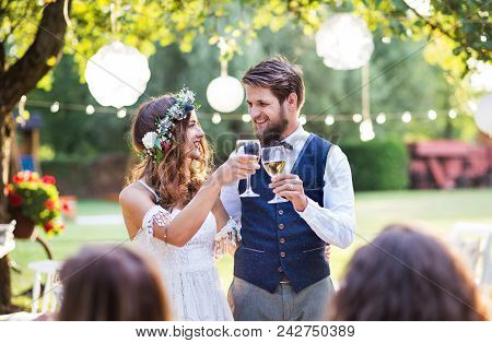 Wedding Reception Outside In The Backyard. Bride And Groom Clinking Glasses.