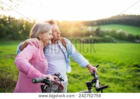 Beautiful Senior Couple Outside In Spring Nature, Standing With Bicycles On Grassland.