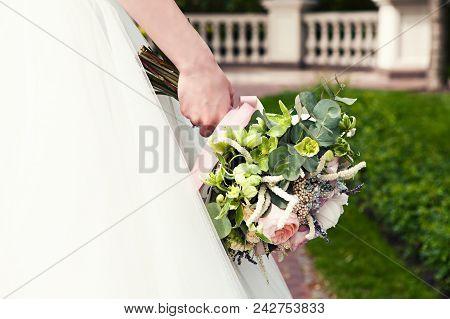 Bride Holds A Wedding Bouquet, Wedding Dress, Wedding Accessories. Wedding Ceremony Concept.