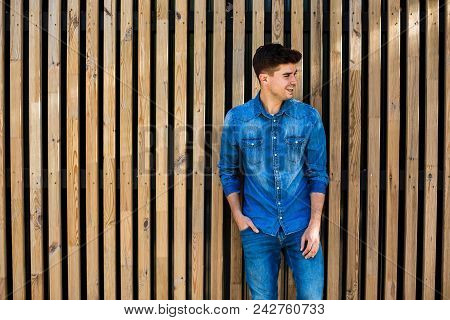 Cool Guy In Jeans Outfit On Wooden Background