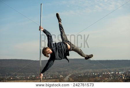 Pole Dance Sport. Strong Man Dancer Workout On Pole. Sexy Macho Man Fly On Blue Sky Background. Athl