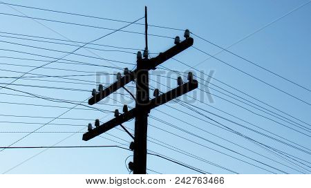 Old Wooden Electric Pole With Linear Insulators And Electrical Wires