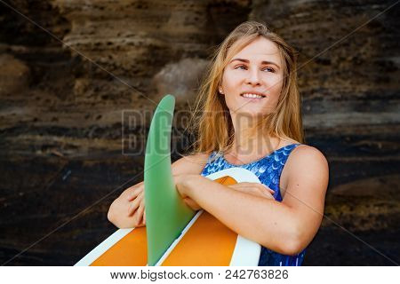 Sporty Girl In Bikini With Surfboard Stand By Black Cliff On Beach. Surfer Woman Look At Sea Surf An