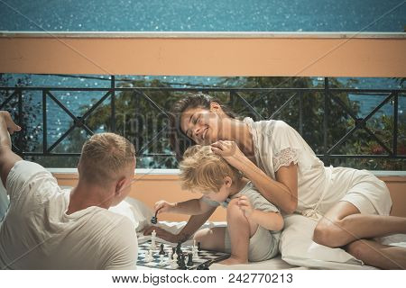 Summer Vacation Of Happy Family. Child Play Chess With Father And Mother. Family Travel With Kid On