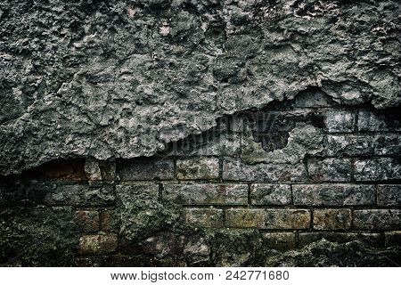 Old Brick Wall With Cracked Fallen Off Plaster. Ancient Abandoned Building. Gloomy Dark Background