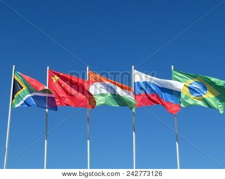 Waving Flags Of The Brics Countries Against The Blue Sky. The Summit Of Brazil, Russia, India, China