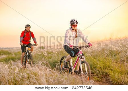 Young Couple Riding the Mountain Bikes in the Beautiful Field Full of Feather Grass at Sunset. Adventure and Family Travel Concept.