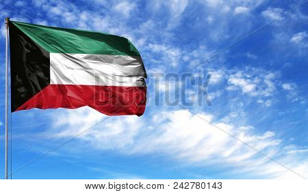 Flag Of Kuwait On Flagpole Against The Blue Sky.