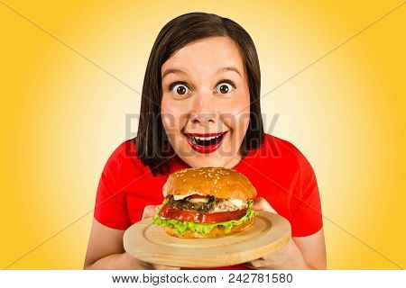 Young Woman Holds Hamburger, Smiles And Looks In Camera. Isolated On Orange Background.
