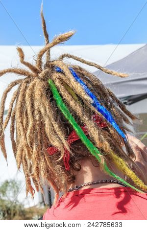 Man with colorful dreadlocks close-up. Hair design, youth hairstyles, African hairstyles, street style poster