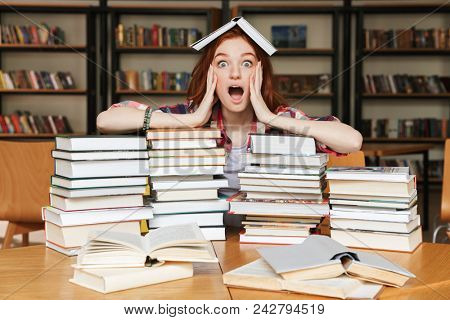Surprised teenage girl sitting at the library table with big stacks of books