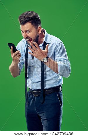 Screaming, Hate, Rage. Crying Emotional Angry Man With Mobile Phone Screaming On Green Studio Backgr