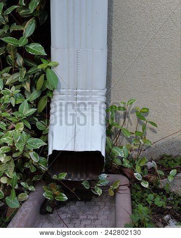 Vertical White Gutter Down Spout Against Concrete House