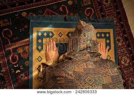 Muslim Woman Praying For Allah Muslim God At Room Near Window. Hands Of Muslim Woman On The Carpet P