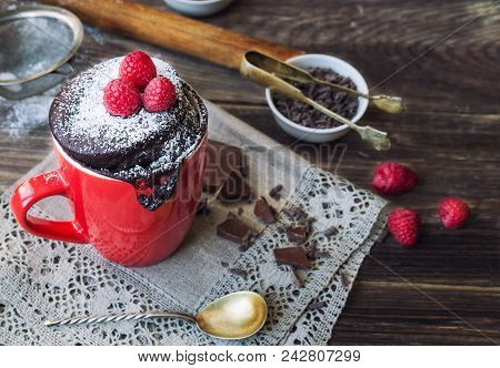 Fresh homemade chocolate cake in mug on rustic wooden background. Cooked in microwave. poster