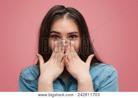 Pretty Shy Brunette In Denim Covering Mouth With Hands Looking Excitedly At Camera On Pink Backdrop.