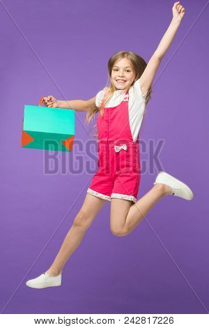 Girl On Smiling Face Carries Shopping Bag And Jumps, Isolated On White Background. Girl Likes To Buy
