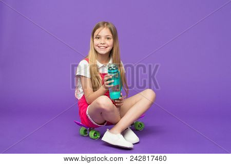 Girl On Smiling Face Holds With Bottle Of Water While Sits On Skateboard, Violet Background. Kid Gir