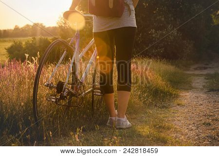 Girl Travel By Bicycle In Sunset. Girl Travel Alone By Bicycle In Countryside Landscape. Traveler Cy