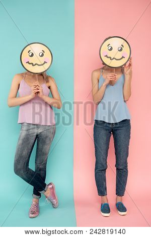 Shamefaced. Full length of two girls expressing embarrassment on blue and pink background poster
