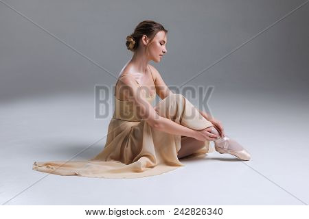 Power Of Dance! Beautiful Graceful Delicate Young Female Ballet Dancer Sitting On The Floor, While P