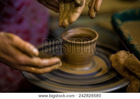 Sculpts in clay pot closeup. Modeling clay close-up. Caucasian man making vessel daytime of white clay in fast moving circle. Art, creativity. Ukraine, cultural traditions. Hobbies poster
