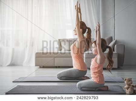 Full Length Of Woman And Her Child Sitting On Their Knees With Their Hands Up. They Are Doing Fitnes