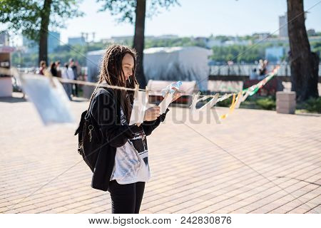 A Girl With Dreadlocks At The Street Exhibition Of Photographs Of Professionals And Non-professional