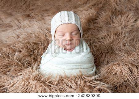 Swaddled newborn sleeping on brown plaid