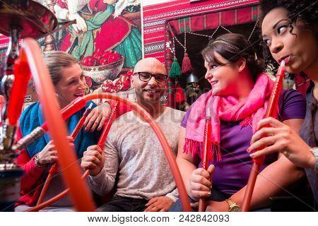 Women and man enjoying recreational shisha in hookah lounge on the weekend