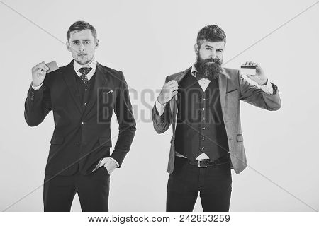 Handsome man face. Businessmen, business partners in suits holding plastic credit cards, isolated on white. Creditors offering to create banking account, get money for business. Credit and banking account concept. poster