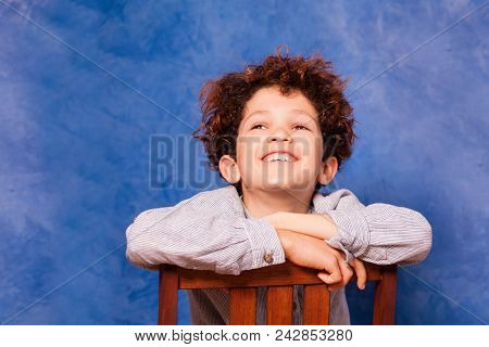 Happy preteen boy with curly hair looking upward while sitting backwards on wooden chair against blue background poster