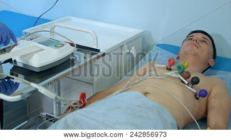 Nurse With Ecg Equipment Making Cardiogram Test To Male Patient