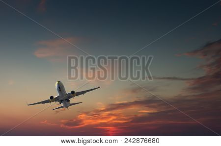 Commercial Airliner Taking Off Or Landing Against Dramatic Red Blue Sky - With Landing Gear Halfway