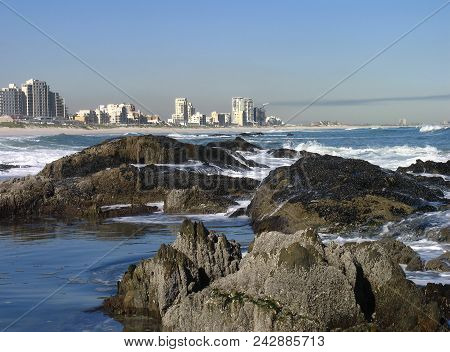 Seascape, With Huge Boulders In The Fore Ground And High Rise Buildings In The Back Ground 03900