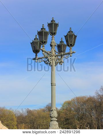 Street Lantern Isolated On Empty Blue Sky Background. Vintage Old Lamppost With Decorative Ornament