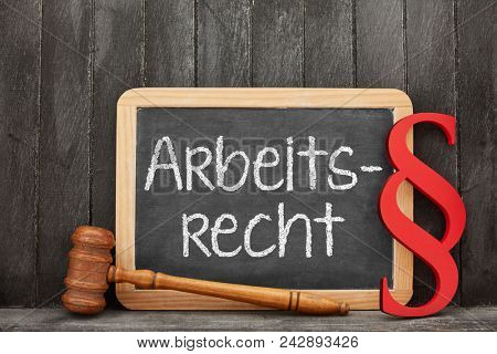 Blackboard with German word Arbeitsrecht (employment law) for specialist lawyer text and law symbols