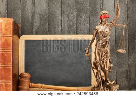 Justitia in front of empty blackboard and judge gavel as law and law concept