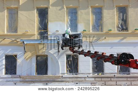 Construction Worker Working On  Facade Renovations Of Historic Old City House Front. Male Worker Pla